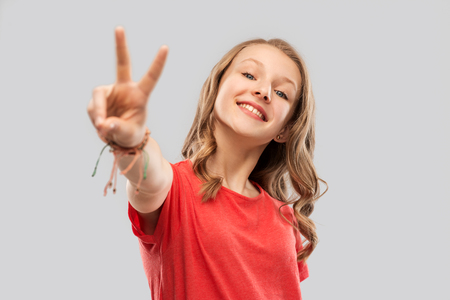 smiling teenage girl in red t-shirt showing peace Standard-Bild
