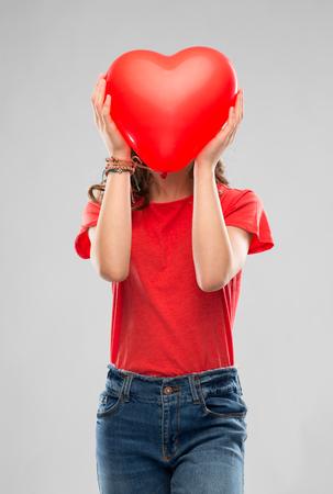 ragazza adolescente con palloncino a forma di cuore rosso