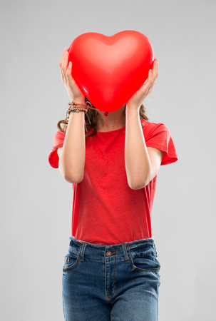 teenage girl with red heart shaped balloon Foto de archivo