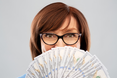 senior woman with hundred dollar money banknotes