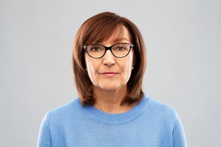portrait of senior woman in glasses over grey