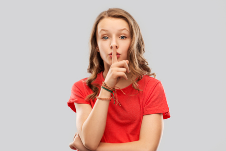 teenage girl in red t-shirt with finger on lips Stock Photo