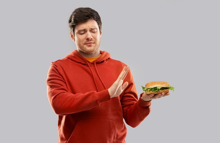 young man refusing from hamburger