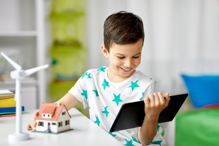 boy with tablet, toy house and wind turbine
