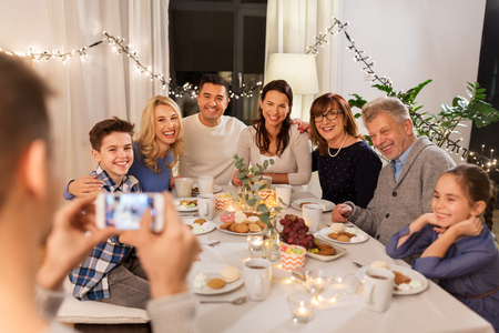family having dinner party and taking selfie