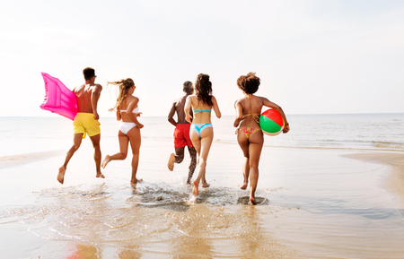 friends run with beach ball and swimming mattress