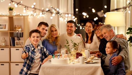 family having birthday party and taking selfie Фото со стока