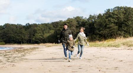happy family running along autumn beach