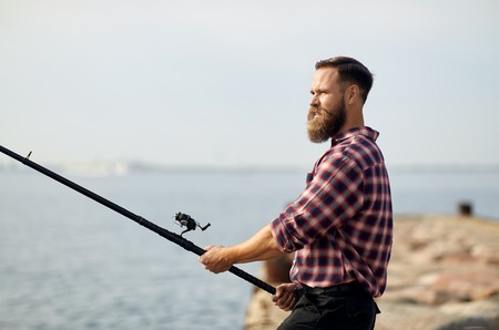 bearded fisherman with fishing rod on pier at sea