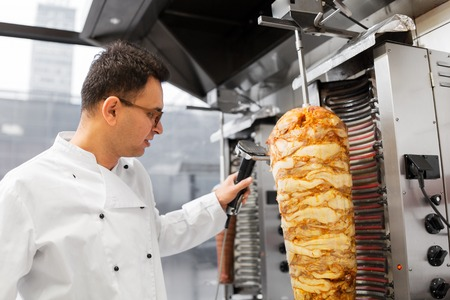 fast food and cooking concept - chef slicing doner meat from rotating spit at kebab shop Stock Photo - 118650606