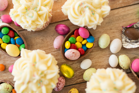 cupcakes with chocolate eggs and candies on table