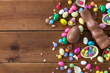 chocolate eggs, easter bunny and candies on wood Stock Photo