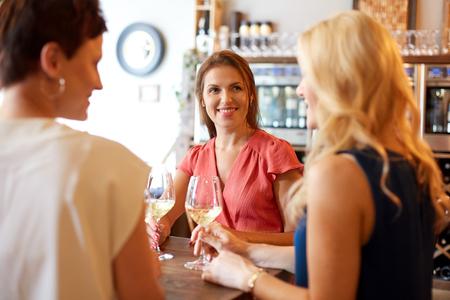 happy women drinking wine at bar or restaurant