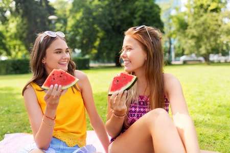 teenage girls eating watermelon at picnic in park