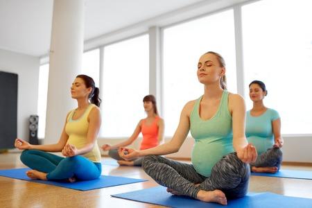 happy pregnant women meditating at gym yoga Stock Photo