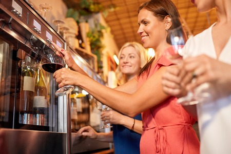 happy women pouring wine from dispenser at bar Stock Photo