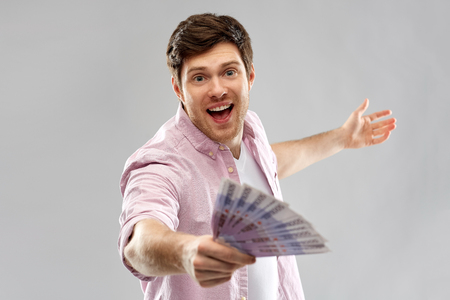 happy young man with fan of euro money