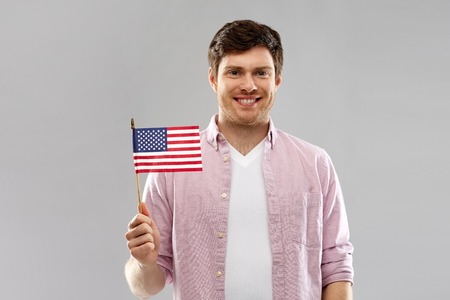 happy man with american flag over grey background