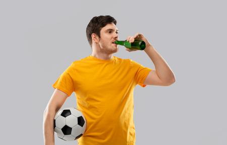 man or football fan with soccer ball drinking beer Фото со стока
