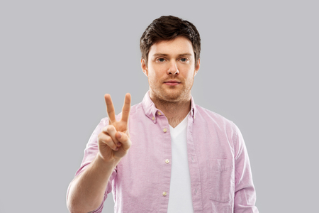 young man showing two fingers over grey background