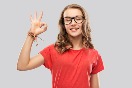 smiling student girl in glasses showing ok sign Stock Photo