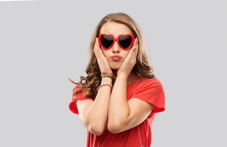girl in red heart shaped sunglasses pouting Imagens