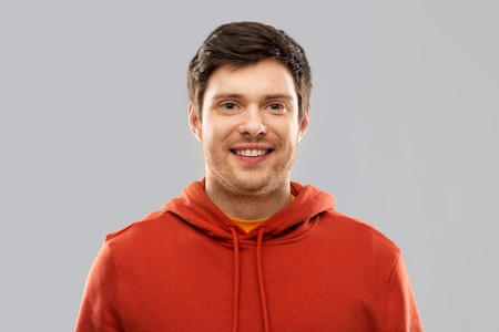 smiling young man in red hoodie over grey Archivio Fotografico