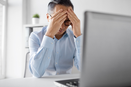 stressed businessman with laptop working at office