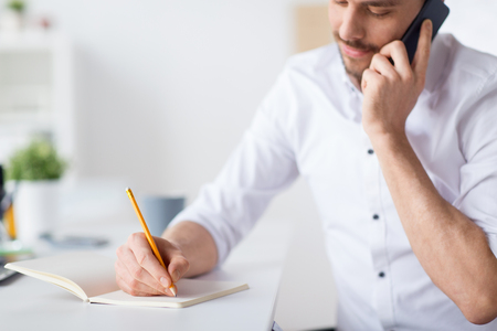 businessman calling on cell writing to notebook Stock Photo