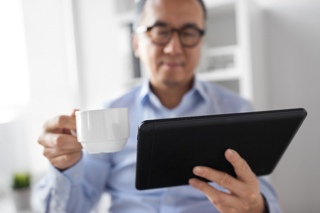 business, people and technology concept - close up of asian businessman with tablet computer drinking coffee at office