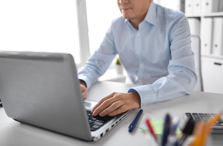 business, people and technology concept - close up of businessman with laptop computer working at office Stock Photo