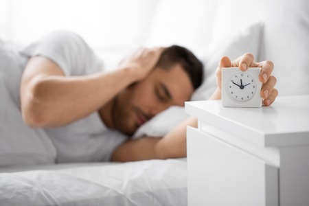 morning and people concept - close up of sleepy young man in bed reaching for alarm clock on bedside table at home Stock Photo