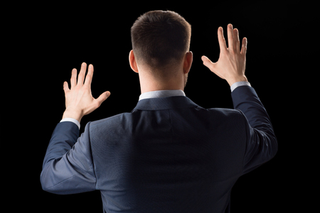 business, technology and augmented reality concept - businessman in suit working with invisible virtual screen over black background Stock Photo