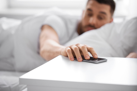 technology and people concept - close up of sleepy young man reaching for smartphone on bedside table from bed at home in morning