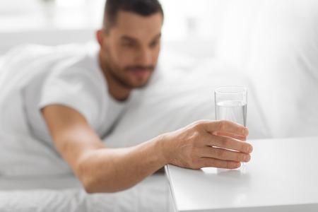 Concepto de mañana e hidratación - cerca del hombre sediento alcanzando un vaso de agua en la mesita de noche desde la cama en casa