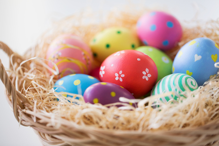 easter, holidays, tradition and object concept - close up of colored eggs in basket Stock Photo
