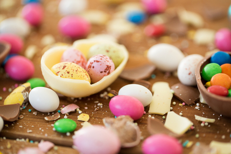 easter, junk-food, confectionery and unhealthy eating concept - close up of chocolate eggs and candy drops on table