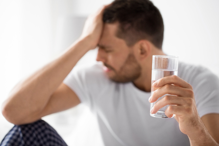 people, health and hydration concept - close up of unhealthy man suffering from hangover with glass of water in morning