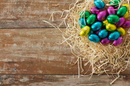 easter, confectionery and holidays concept - chocolate eggs in foil wrappers in straw nest on wooden background