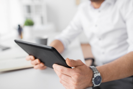 technology, business and people concept - close up of businessman with tablet pc at office