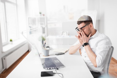 business, deadline and stress concept - tired businessman rubbing eyes at office Stock Photo