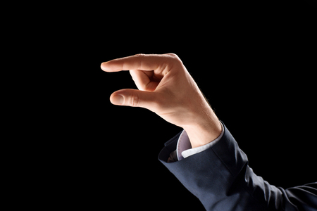 business, gesture and finger language concept - hand of businessman holding something imaginary or showing some small thing over black background 版權商用圖片 - 118909044