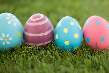 easter, holidays and tradition concept - row of colored eggs on artificial grass