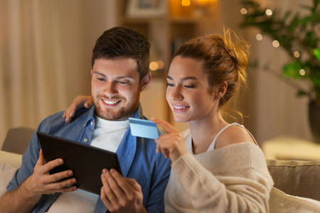 technology, internet banking and people concept - happy couple using tablet computer and credit card at home in evening