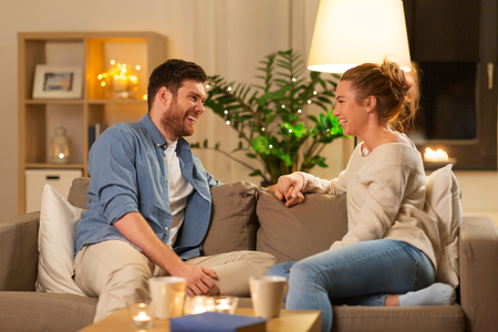 leisure and people concept - happy couple talking at home in evening Stock Photo