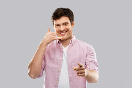 people concept - smiling young man showing phone call gesture and pointing to you over grey background