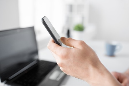 business, communication and technology concept - close up of hand with smartphone at office