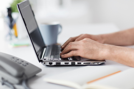 business, people and technology concept - hands typing on laptop computer keyboard at office