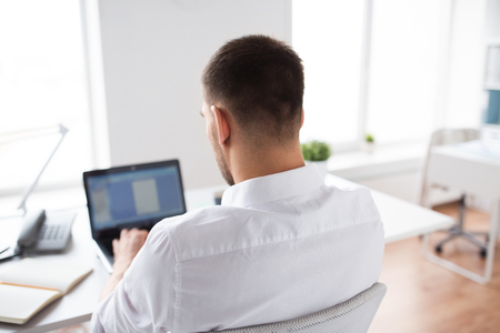 business, people and technology concept - close up of businessman typing on laptop computer at office Stock Photo
