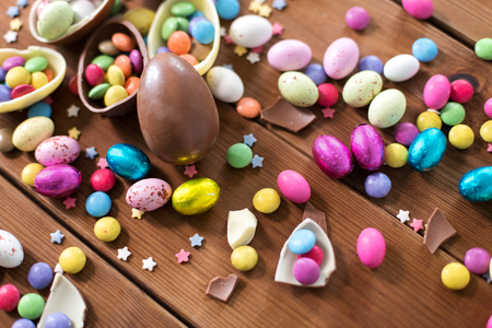 easter, sweets and confectionery concept - close up of chocolate eggs and candy drops on wooden table